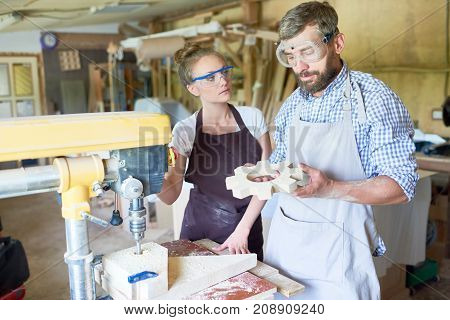 Portrait of bearded carpenter holding wooden part standing by drilling machine with his female assistant in workshop