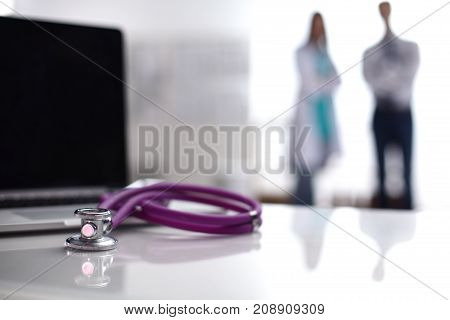 Laptop and medical stethoscope on the desk , doctors standing in the background.