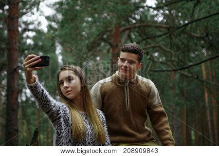 Charming pretty girl holding mobile phone while taking selfie posing together with her smiling boyfriend over beautiful landscape with pines in background. People nature and modern technology