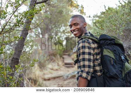 Smiling young African man wearing a backpack standing on a trail while hiking alone in the hills on a sunny day