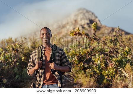 Portrait of a smiling young African man wearing a backpack standing on a trail while hiking alone in the hills on a sunny day