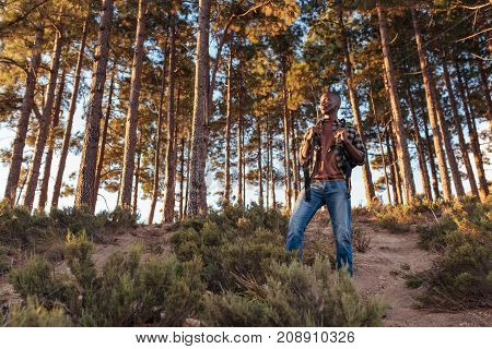 Young African man wearing a backpack standing on a trail while hiking alone in the forest on a sunny day