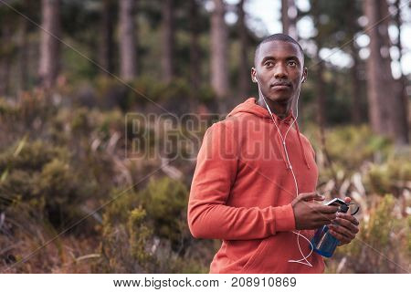 Focused young African man in a hoodie standing on a trail in the forest preparing a music playlist before a run