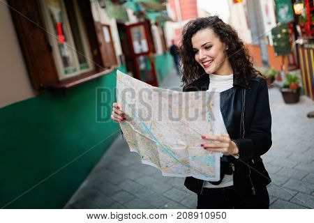 Young beautiful woman looking at city map for directions