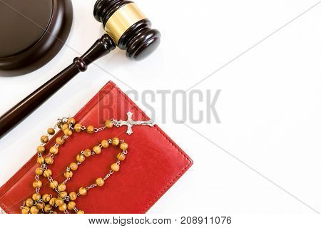 judge's gavel and rosary beads on white background