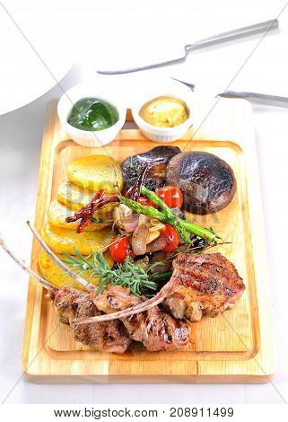 close up of Grilled lamb chops on wood plate