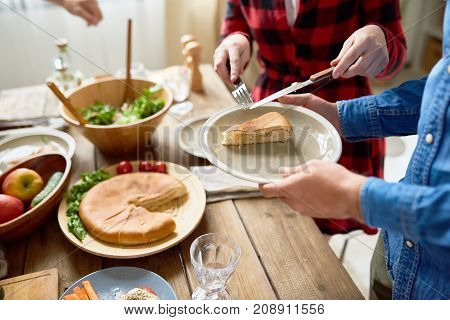 Mid section portrait of modern young couple standing at festive dinner table  serving  food  during family celebration