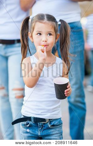 little girl is walking and eating ice cream