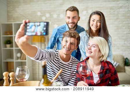 Portrait of four happy friends taking selfie at dinner table while celebrating holiday together at home