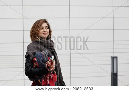 Lifestyle portrait of positive stylish teenage girl wearing trendy black leather jacket and warm woolen scarf posing at blank tile wall with copy space for your text or advertising information