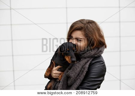 People animals breeding friendship loyalty devotion and happiness concept. Close up shot of fashionable young Caucasian female hugging tight her pet dog feeling strong affection and love