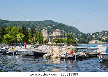 Como Italy - May 27 2016: Yachts and houses along Lake Como in Como town Lombardy region of Italy Europe. Volta Temple (Tempio Voltiano) in the center.