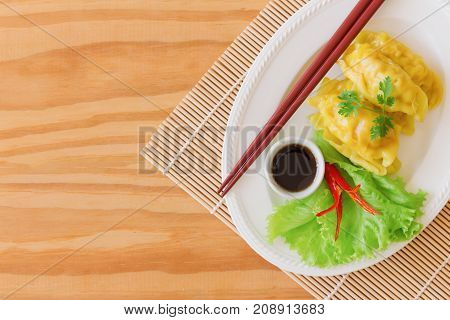 Homemade minced pork or shrimp dumpling and dipping soy sauce on wood table in top view flat lay with copy space. Delicious dumpling or dim sum for breakfast or dinner. Dim sum is Chinese food. Dim sum or dumpling ready to served.