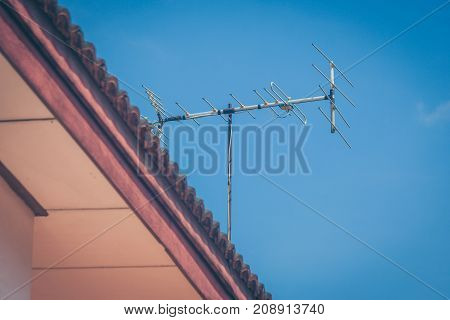 TV antenna on roof of house with blue sky background in vintage style.