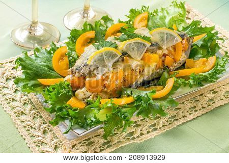 Mackerel baked with tomatoes and cheese served on lettuce with lemon and fresh tomatoes decorated with parsley. Festive table setting: plate on lacy napkin glasses of wine on green background