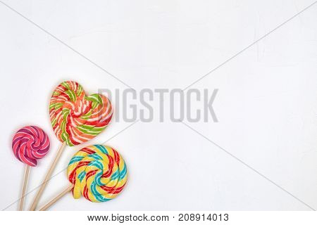 Swirl rainbow lollipop candy on white background copyspace