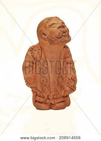 A ceramic brwon netske figurine over whte background