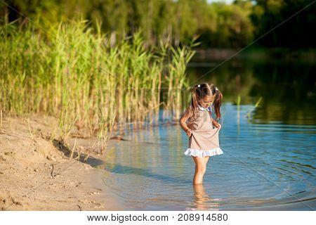 beautiful girl in a dress walking on the lake and having fun