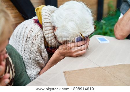 Portrait of old lady laughing hysterically hiding her face while playing card game with friends outdoors
