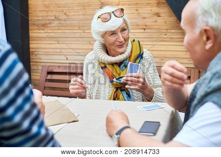 Portrait of cheerful seniors playing card game at lunch table on outdoor terrace, focus on elegant old lady smiling happily
