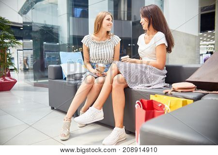 Portrait of two beautiful young women chatting in shopping mall, sitting on couch in hall relaxing with coffee