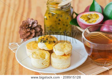 Homemade plain scones with homemade passion fruit jam and tea. Scone is English traditional pastry for coffee or tea time. Delicious scone and passion fruit jam on wood table with copy space. Scones and passion fruit jam read y to served.