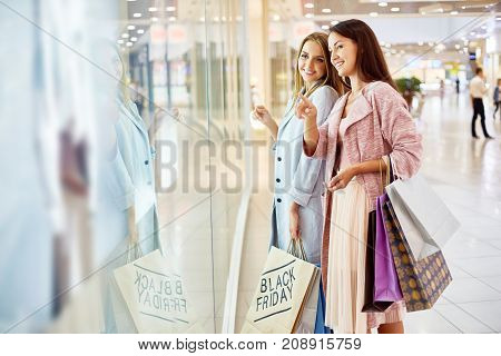 Portrait of two beautiful women  in shopping center looking at window displays of store and smiling, choosing clothes on Black Friday