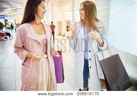 Portrait of two beautiful women shopping in mall chatting happily walking past window displays