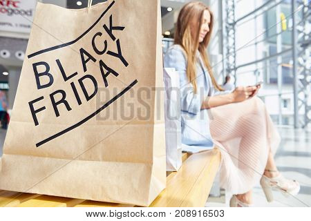 Portrait of fashionable young woman using smartphone while sitting on bench in shopping mall, BLACK FRIDAY paper back in focus