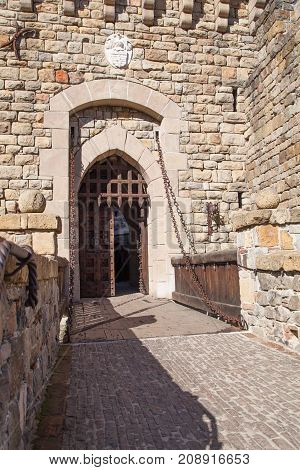 A brick walkway leading to a wooden drawbridge before a iron gate and thick wooden door of a castle entrance.