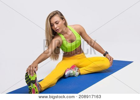 Young woman in bright sportswear sitting on map warming up muscles on white background.