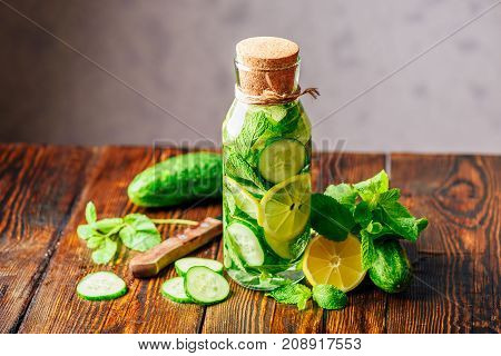 Bottle of Infusion with Sliced Lemon Cucumber and Sprigs of Mint. Ingredients and Knife on Table. Copy Space.