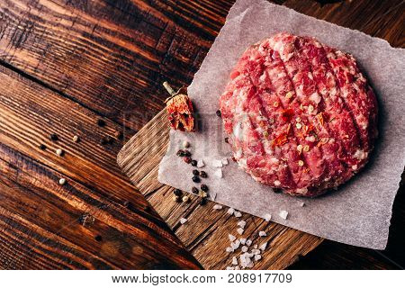 Raw Round Patty with Spices on Wax Paper for Burger. View from Above.