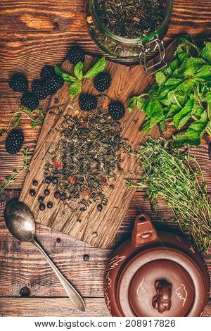 Heap of Dry Green Tea and Fresh Blackberries on Wooden Cutting Board. Bundles of Mint and Thyme Leaves. Clay Kettle. View from Above.