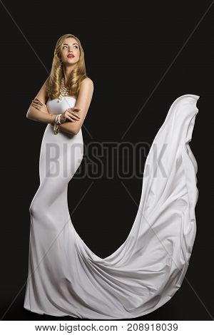 Fashion Model Wedding Bride Dress Woman Beauty in White Gown Long Flying Silk Train over black background