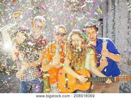 Young friends having a big street party - Group of happy people throwing confetti playing guitar singing and dancing on the street - Focus on confetti