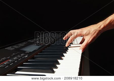 Hands of musician play the keys of the electronic synthesizer on a black background