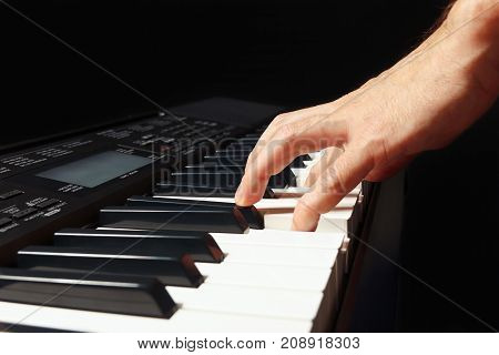 Hand of musician play the keys of the digital piano on a black background
