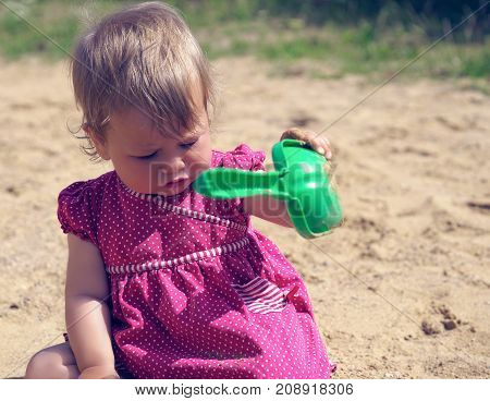 Little girl is playing with a shovel in the sandbox on a sunny summer day. The concept of education and child development.
