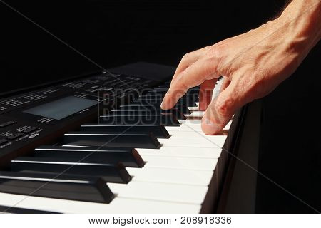 Hand of pianist playing the synth on a black background