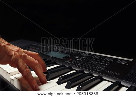 Hand of pianist playing the digital piano on a black background
