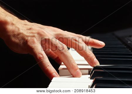 Hand of pianist play the keys of the electronic organ on a black background close up