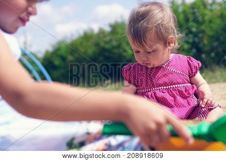 Two little girls play in the sandbox on a hot summer day. The eldest girl in the foreground plays with a shovel the younger looks down.