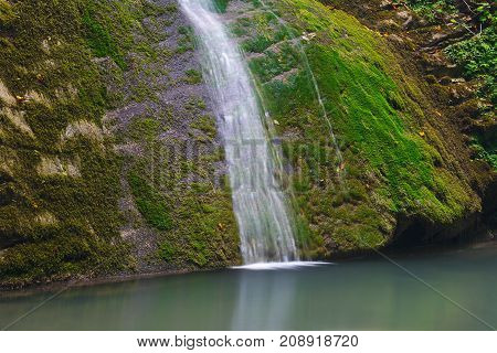 Cliffs overgrown with moss with a waterfall flowing down