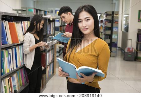 Young student reading book in University library