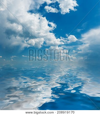 Panorama of vast blue summer sky with fluffy white cumulus clouds reflected in a water surface with small waves