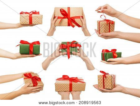 Set of white woman's hands holding handmade, creative present boxes wrapped in paper with ribbon for christmas or new year. Isolated at white background