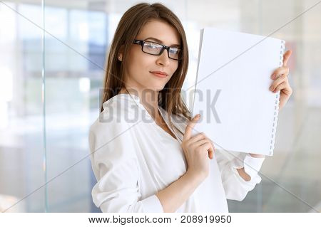 Business woman keeping copy space area while standing in the office.