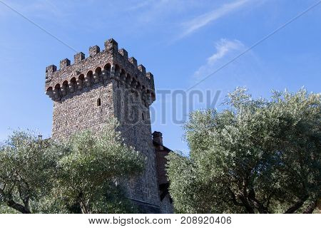 A brick and rock castle turret standing tall in the blue sky surrounded by olive trees.