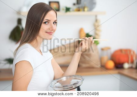 Young  woman cooking in a kitchen. Housewife tasting soup by wooden spoon.